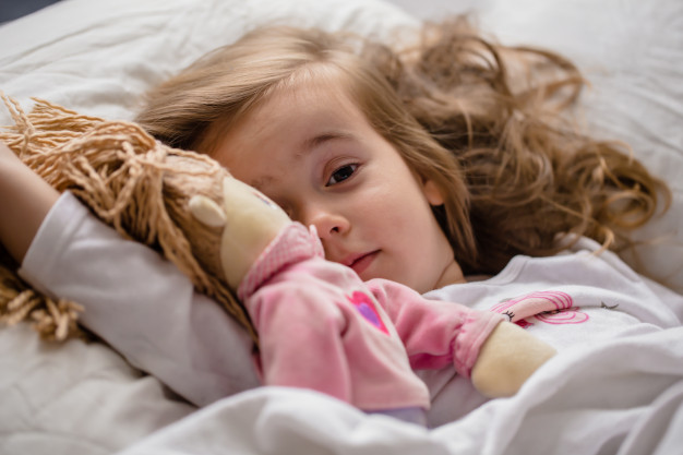 dziewczynka leży w łóżku z lalką