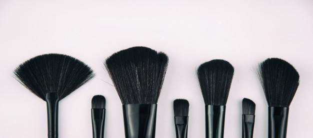 czarne akcesoria do makijażu na jasnoróżowym tle